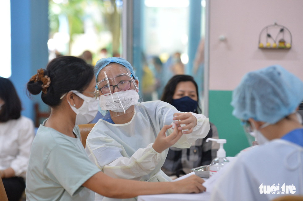 A medical worker gives consultancy to a woman before COVID-19 injection at a vaccination site at 19/5 Kindergarten in District 1, Ho Chi Minh City, June 22, 2021. Photo: Tu Trung / Tuoi Tre