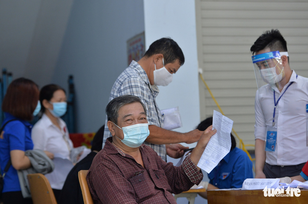 Do Xuan Thanh holds his vaccination certificate after getting COVID-19 injection at a vaccination site at 19/5 Kindergarten in District 1, Ho Chi Minh City, June 22, 2021. Photo: Tu Trung / Tuoi Tre