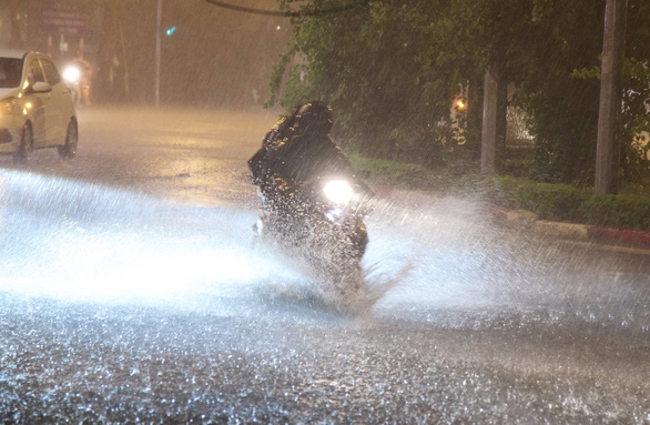 Evening downpour soothes heat, brings floods to Hanoi streets