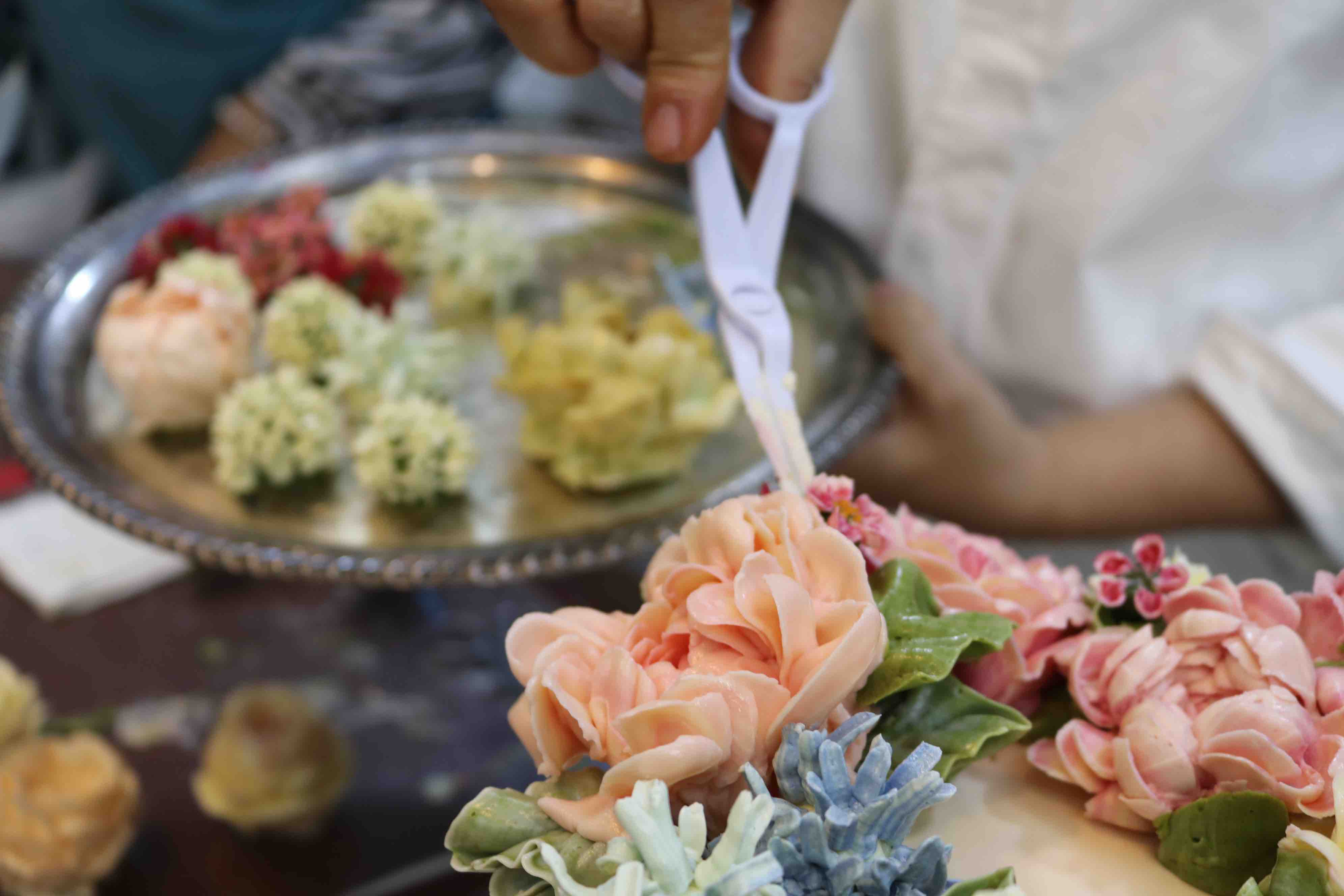 Tran showcases her skills in placing flowers on a cake at her workshop in Ho Chi Minh City. Photo: Hoang An / Tuoi Tre