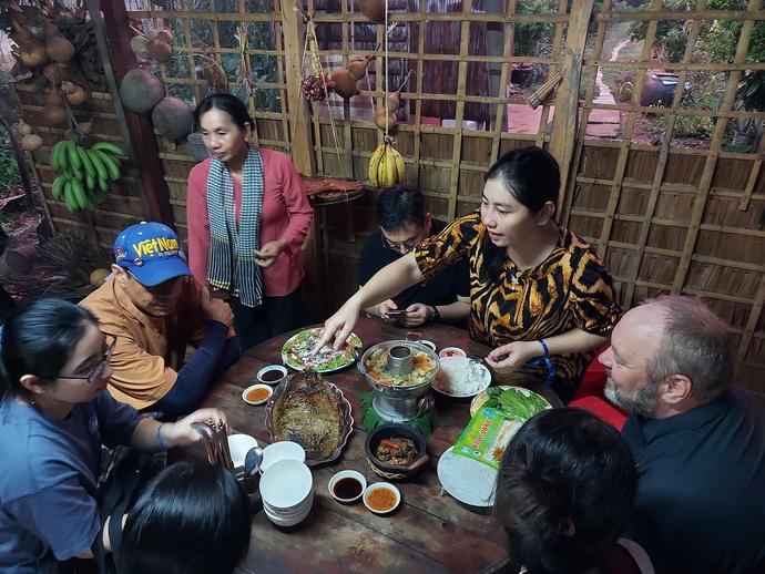 Visitors enjoy a hot pot meal prepared by Bay Muon. Photo: Chi Cong / Tuoi Tre