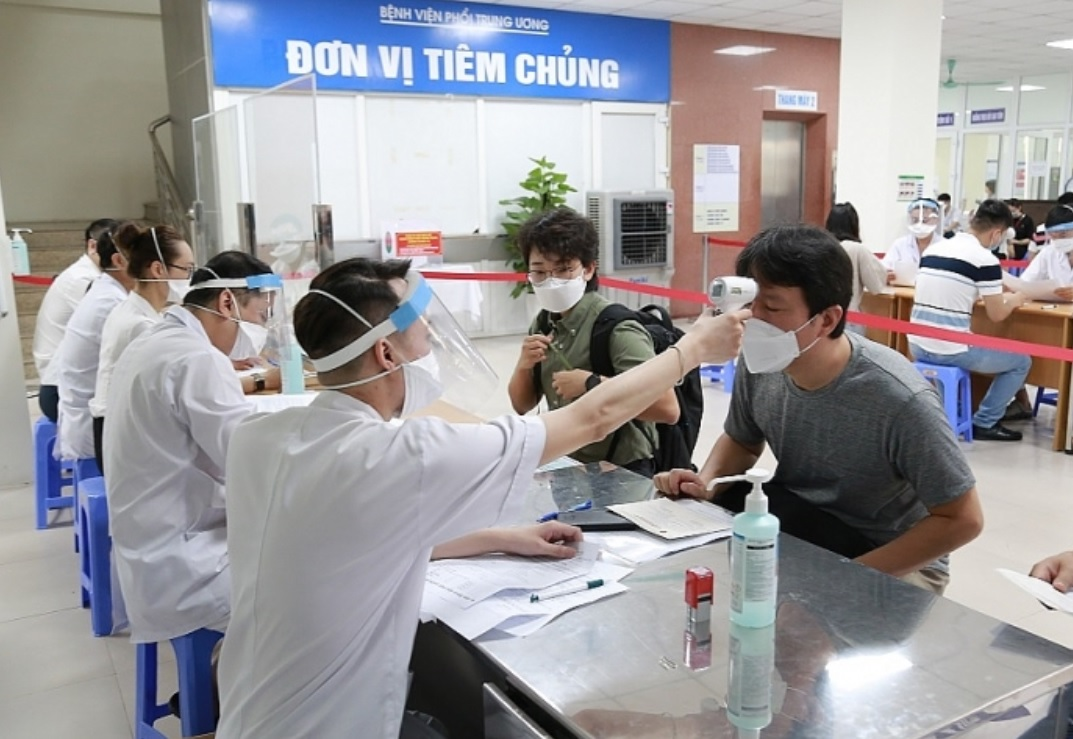 A foreign reporter has his body temperature measured before COVID-19 vaccine injection at the National Lung Hospital in Hanoi, June 27, 2021. Photo: Ministry of Health