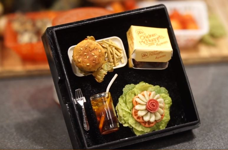 A set of meal including chicken nuggets, a hamburger, salad and a glass of drink are made from clay by Nguyen Nhu Quynh. Photo: Duong Lieu / Tuoi Tre