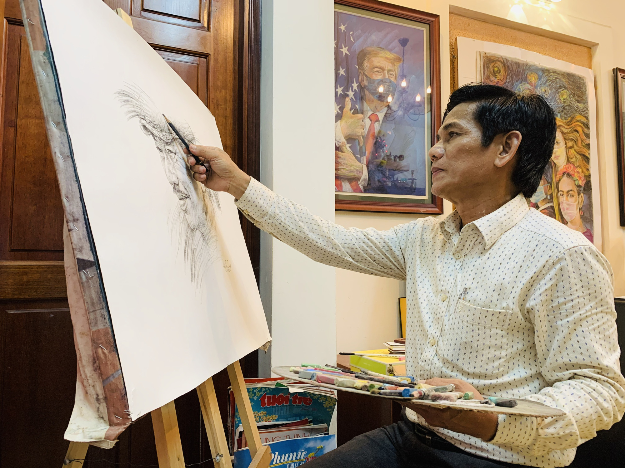 Artist Le Sa Long completes a sketch in his studio in Ho Chi Minh City. Photo: Phuong Nam / Tuoi Tre