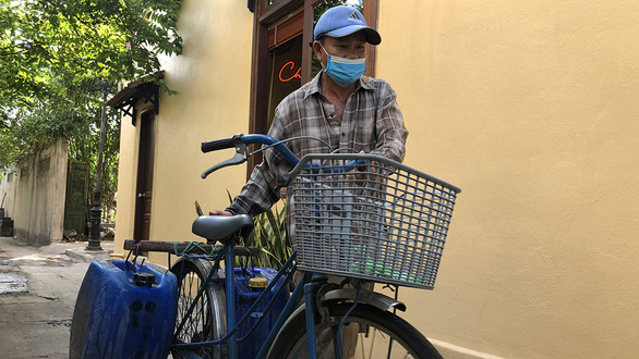 Noi transports his two cans of well water to his customers on a daily basis. Photo. B.D. / Tuoi Tre
