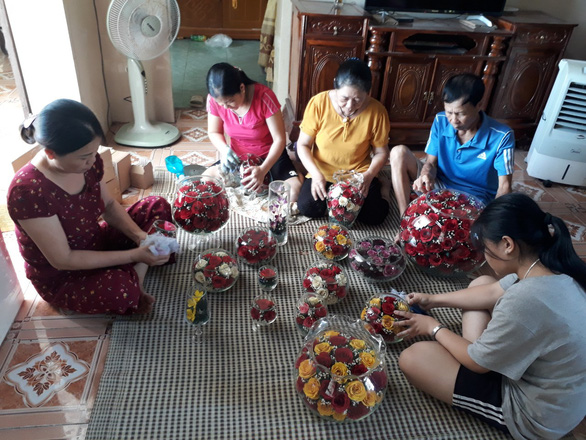 Le Thi Viet (center) has passed on her flower embalming skills and provided jobs for local residents in northern Thanh Hoa Province. Photo: Tam Le / Tuoi Tre