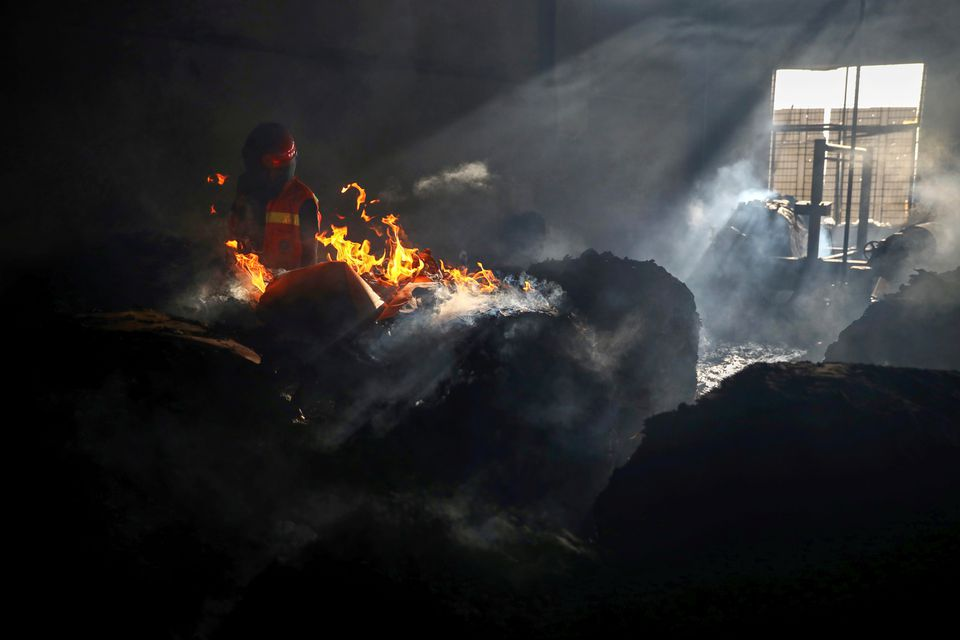 A firefighter tries to extinguish fire inside the building after a fire broke out at a factory named Hashem Foods Ltd. in Rupganj of Narayanganj district, on the outskirts of Dhaka, Bangladesh, July 9, 2021. Photo: Reuters