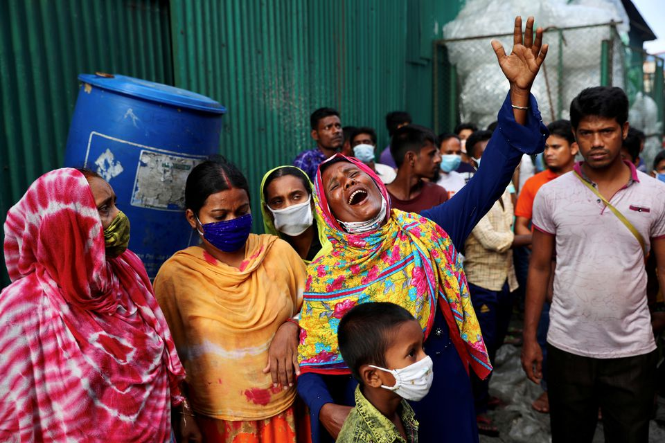 Unidentified relatives of the victims mourn at the site after a fire broke out at a factory named Hashem Foods Ltd. in Rupganj of Narayanganj district, on the outskirts of Dhaka, Bangladesh, July 9, 2021. Photo: Reuters