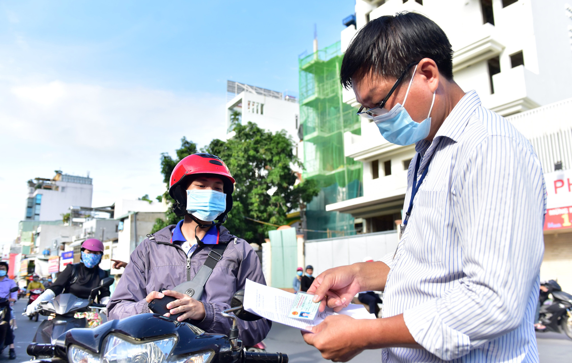 An officer checks personal documents belonging to a commuter on a street in Phu Nhuan District, Ho Chi Minh City, July 9, 2021. Photo: Duyen Phan / Tuoi Tre
