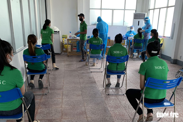 This image shows workers at a workshop of Chingshan Vietnam Co., Ltd. waiting for their samples to be taken for COVID-19 testing. Photo: B.A. / Tuoi Tre