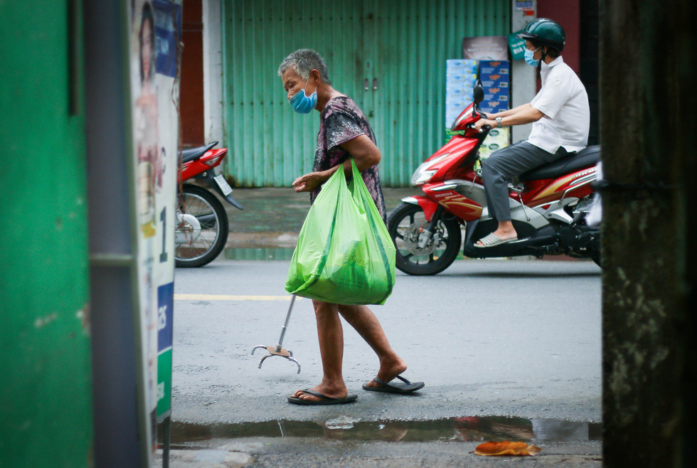 An elder woman walks with a crutch while holding a bag of necessities on Ton Dan Street of District 4. Photo: Chau Tuan / Tuoi Tre