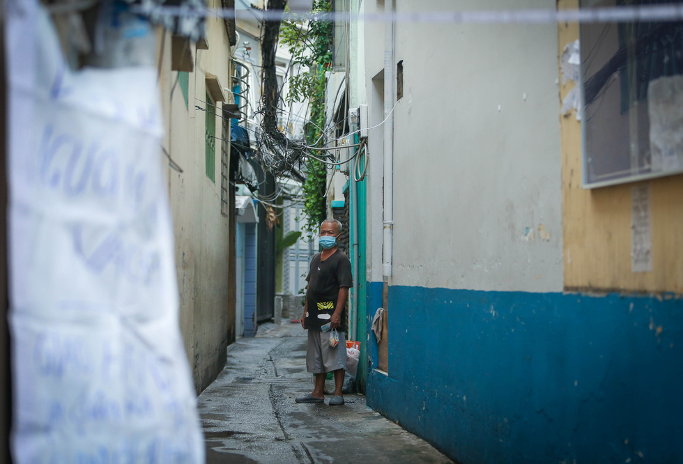 A man is seen on a desolated alley of Ton Dan Street, District 4, during the elevated social distancing mandate in Ho Chi Minh City. Photo: Chau Tuan / Tuoi Tre
