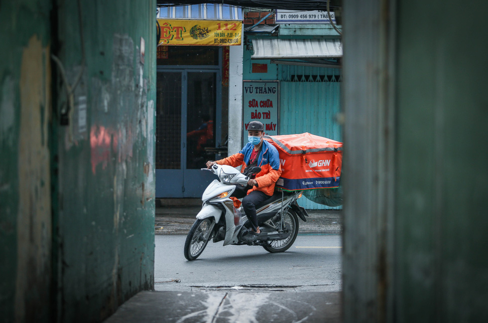 A delivery worker rides his bike on Ton Dan Street, District 4 during the elevated social distancing mandate in Ho Chi Minh City. Photo: Chau Tuan / Tuoi Tre