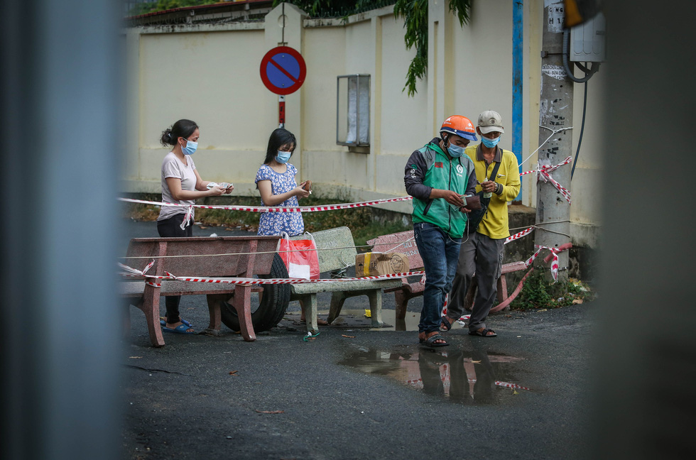 Residents in a lockdown area of Ho Chi Minh City receive items from delivery workers. Photo: Chau Tuan / Tuoi Tre