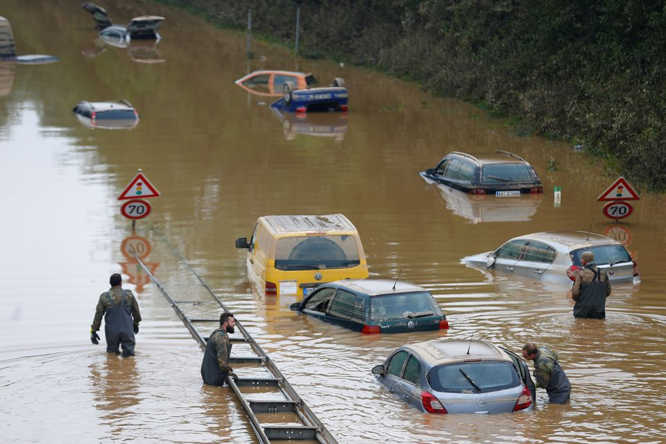 Members of the Bundeswehr forces, surrounded by partially submerged cars, wade through the flood water following heavy rainfalls in Erftstadt-Blessem, Germany, July 17, 2021.  Photo: Reuters