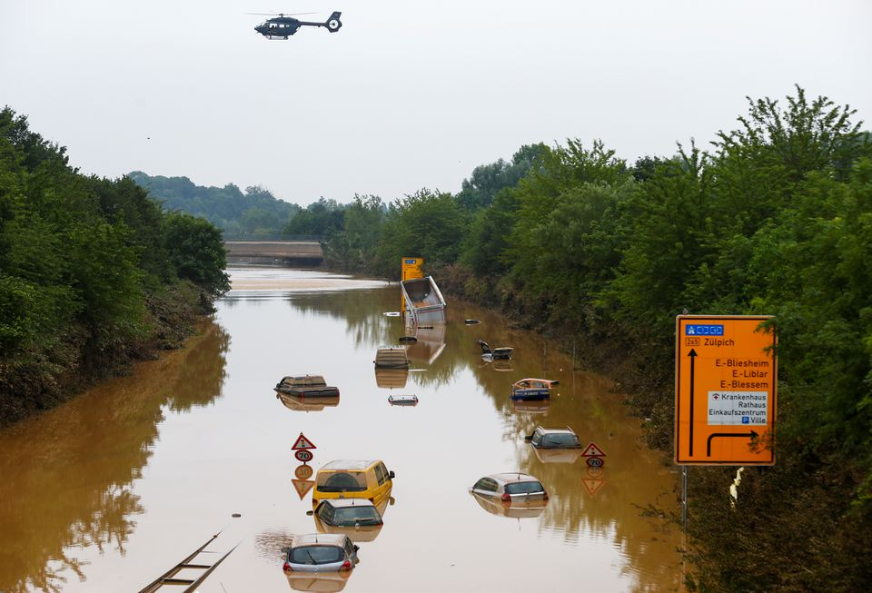 A helicopter flies above cars partially submerged in floodwaters on the road following heavy rainfalls in Erftstadt-Blessem, Germany, July 17, 2021. Photo: Reuters