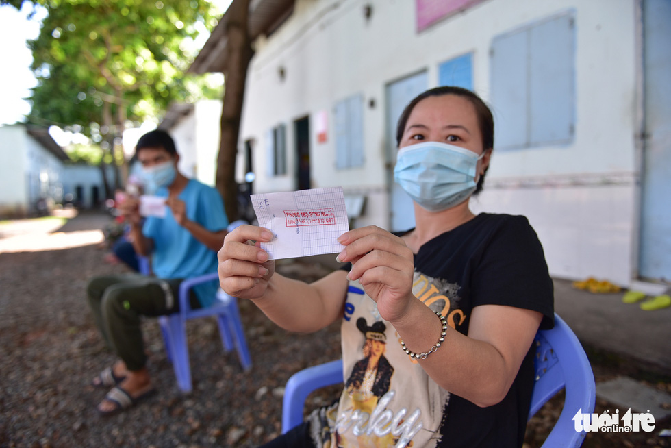 Vuong My Phuong, a resident in Binh Tan District, Ho Chi Minh City receives the gift ticket from from charity initiative 'Nghia tinh mua dich,' July 17, 2021. Photo: Ngoc Phuong / Tuoi Tre