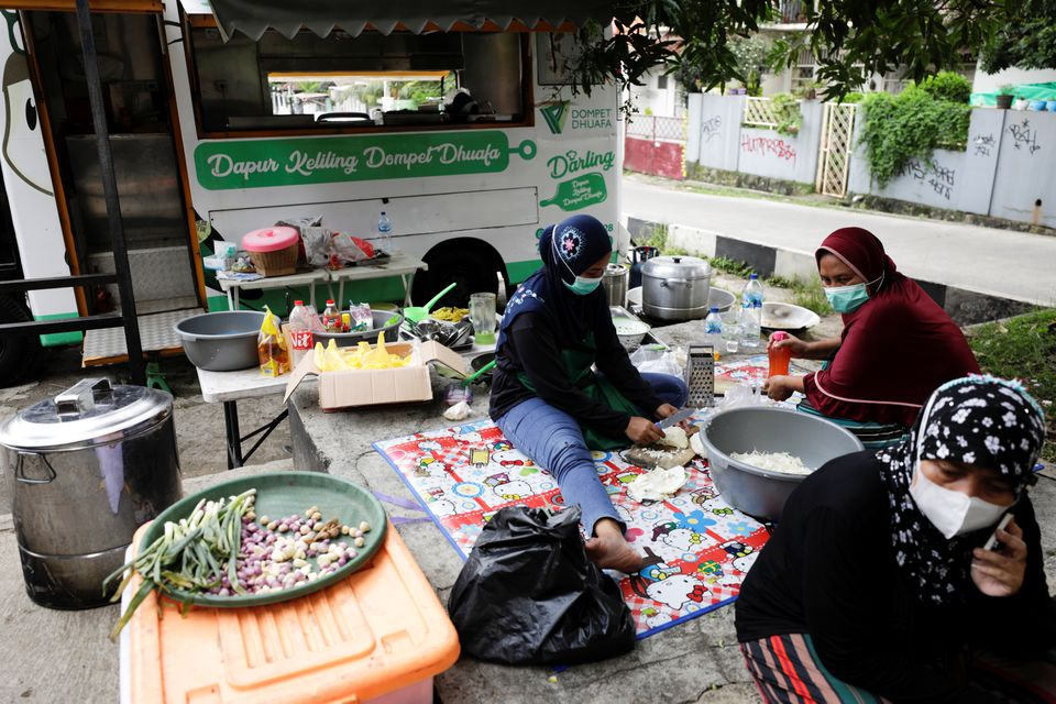 Volunteers of Indonesian NGO Dompet Dhuafa prepare free food to be distributed to coronavirus disease (COVID-19) patients undergoing self-isolation in South Tangerang, on the outskirts of Jakarta, Indonesia, July 11, 2021. Picture taken July 11, 2021. Photo: Reuters