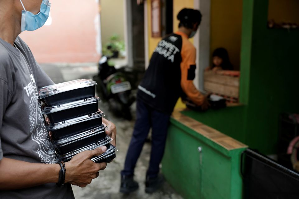 Volunteers of Indonesian NGO Dompet Dhuafa distribute free food to coronavirus disease (COVID-19) patients undergoing self-isolation in South Tangerang, on the outskirts of Jakarta, Indonesia, July 11, 2021. Picture taken July 11, 2021. Photo: Reuters