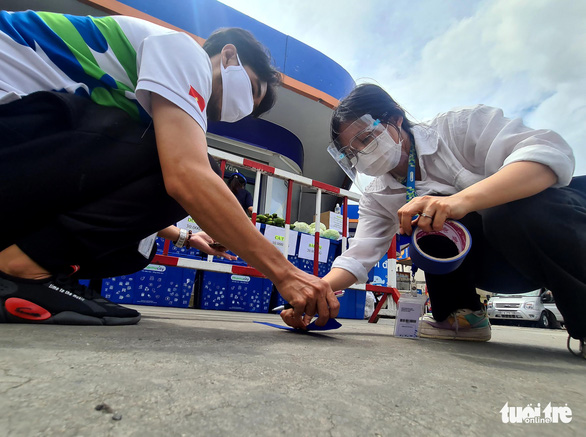 Staffers of a drugstore in Ho Chi Minh City use tapes to mark standing spots of safe distances for customers coming to a temporary grocery stall in Ho Chi Minh City, July 18, 2021. Photo: Ngoc Hien / Tuoi Tre