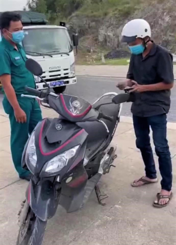 This screenshot from Tran Le Huu Tho's video shows T.V.E. exhibiting personal documents to the functional force at a COVID-19 checkpoint in Vinh Hoa Ward, Nha Trang City, Khanh Hoa Province, Vietnam, July 18, 2021.