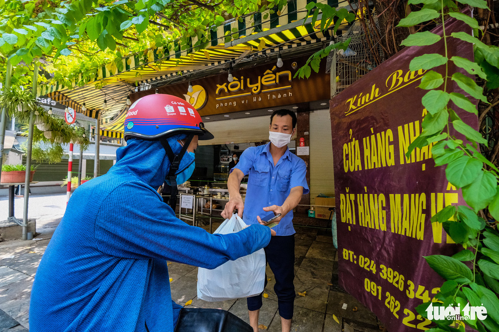 Customers of a food stall in Hanoi take his food from the seller, July 19, 2021. Photo: Nam Tran / Tuoi Tre