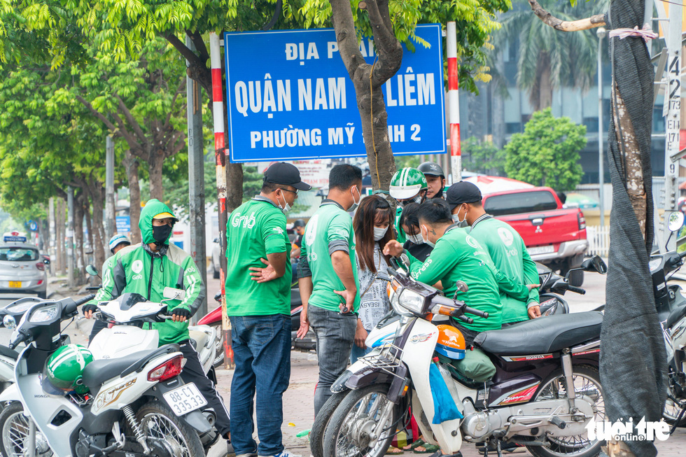 Ride-hailing drivers gather on Pham Hung Street, Nam Tu Liem District, Hanoi, after a social distancing mandate was introduced in the city, July 19, 2021. Photo: Pham Tuan / Tuoi Tre