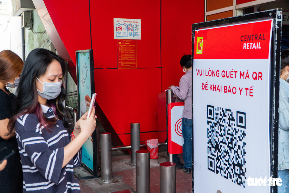 Shoppers scan QR code to file a medical declaration before entering Big C Thang Long Supermarket in Cau Giay District, Hanoi, July 19, 2021. Photo: Pham Tuan / Tuoi Tre