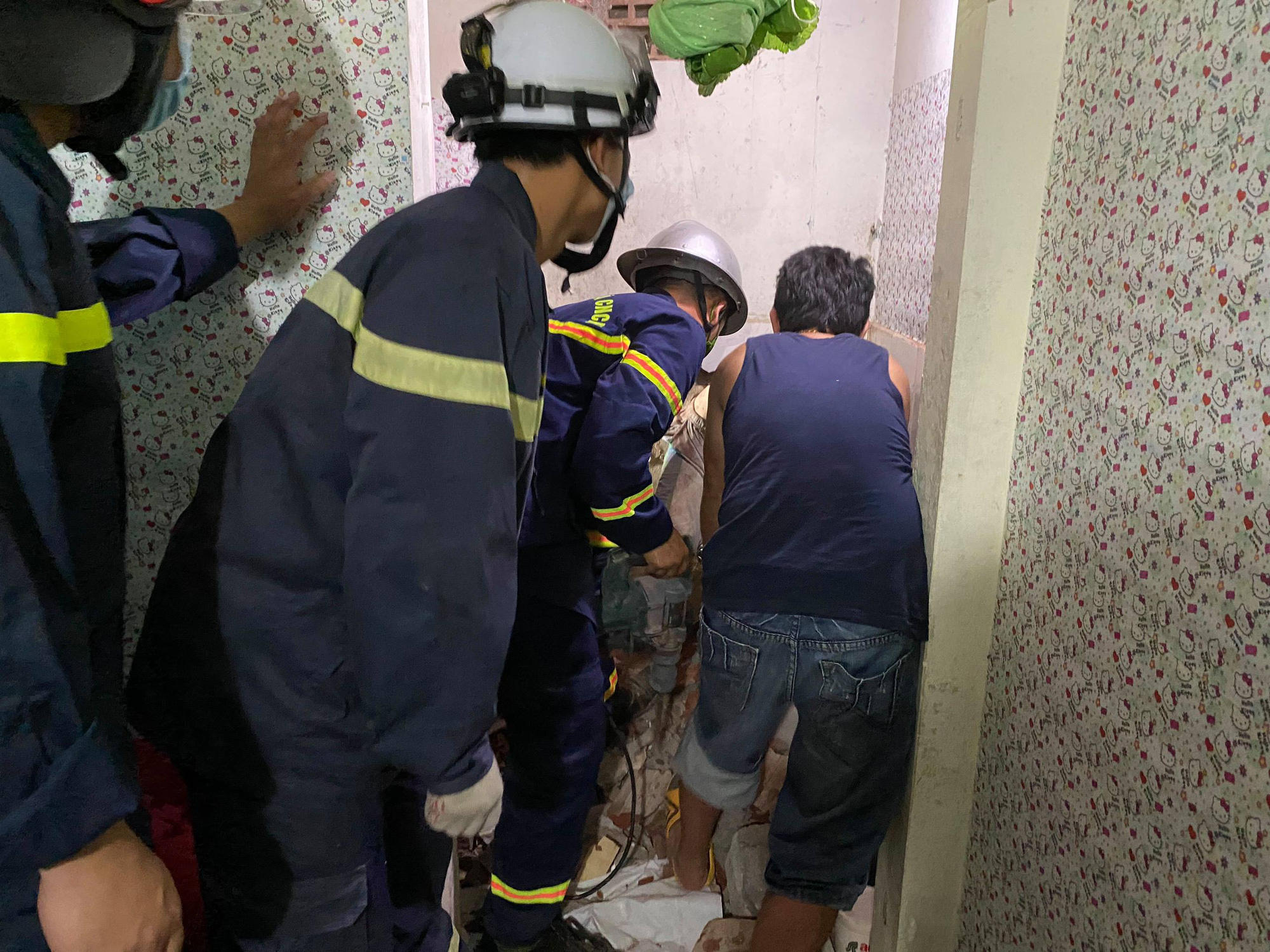 Rescuers try to free C.N.V.T., who was stuck in a narrow gap between two houses in Bac Tu Liem District, Hanoi. Photo: Anh Ha / Tuoi Tre