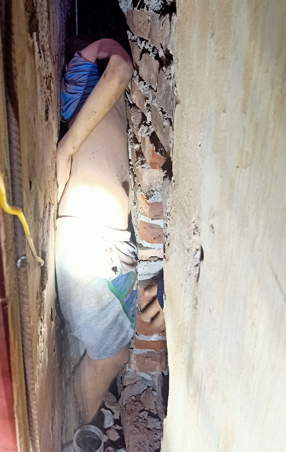 C.N.V.T. is stuck in a narrow gap between two houses in Bac Tu Liem District, Hanoi. Photo: Anh Ha / Tuoi Tre