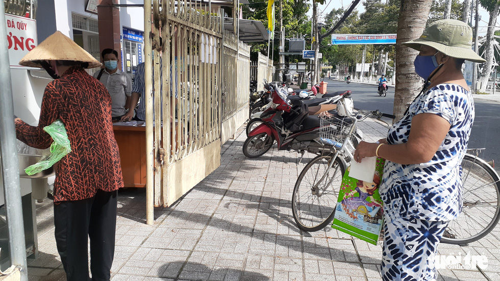 """A woman waits while another is getting her free rice at the """"rice ATM"""" at My Binh Ward, Long Xuyen City, An Giang Province. Photo: Dang Tuyet / Tuoi Tre"""