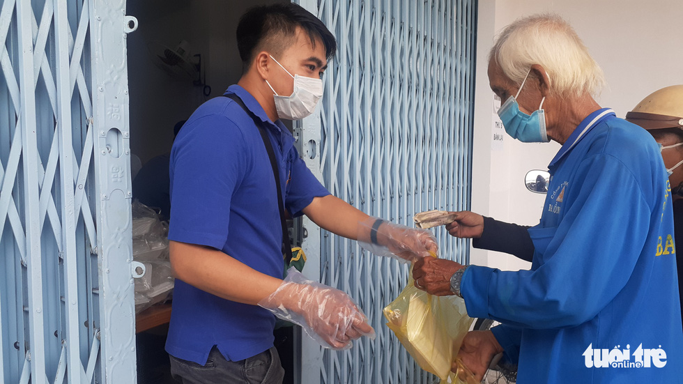 An old man gives VND2,000 to a young man at the restaurant to get his meal during the COVID-19 pandemic in July 2021. Photo: Dang Tuyet / Tuoi Tre