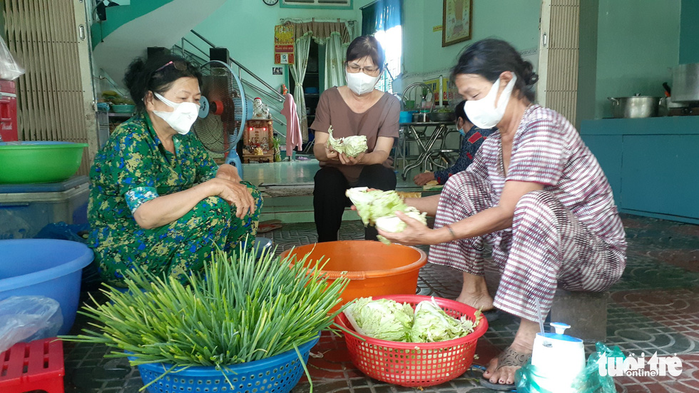 Duong Thu Dong (center) and two women prepare vegetables to make vegetarian food meals to support the poor living in Long Xuyen City during the pandemic. Photo: Dang Tuyet / Tuoi Tre