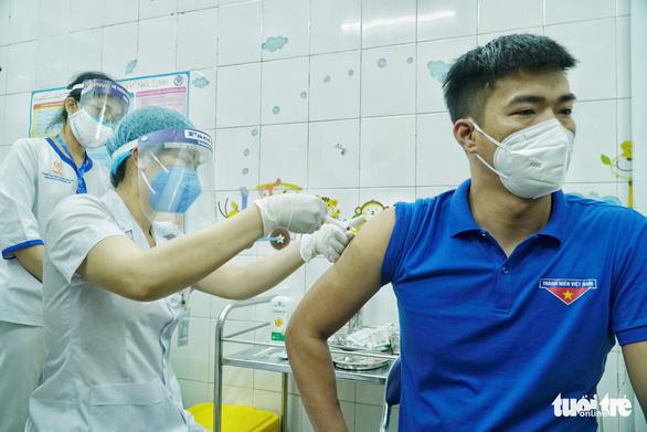 This image shows a man getting vaccination against coronavirus in Vietnam. Photo: Pham Tuan / Tuoi Tre