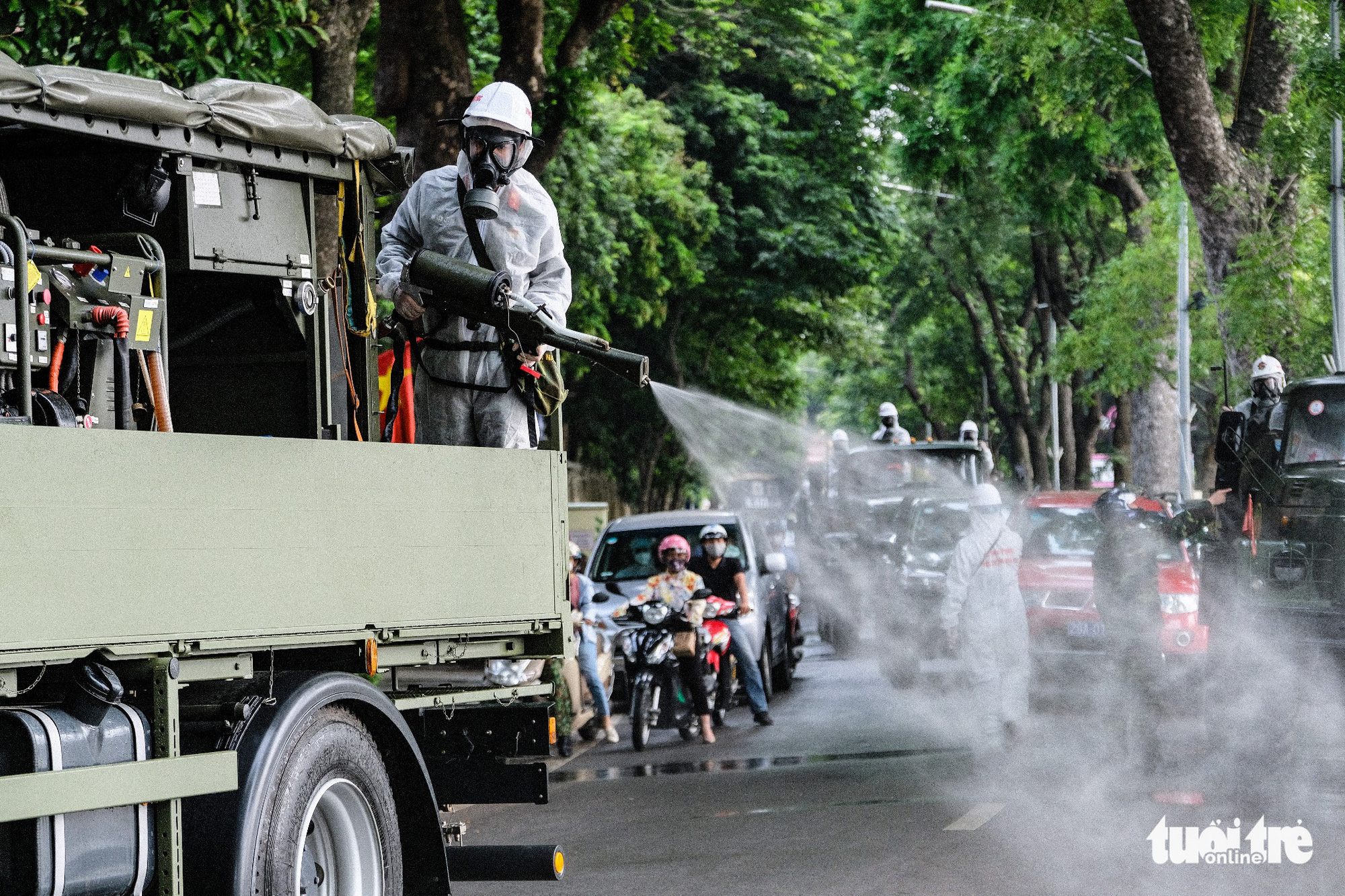 A soldier sprays chemical from atop a specialized vehicle to disinfect a street in Hoan Kiem District, Hanoi, July 26, 2021. Photo: Nam Tran / Tuoi Tre