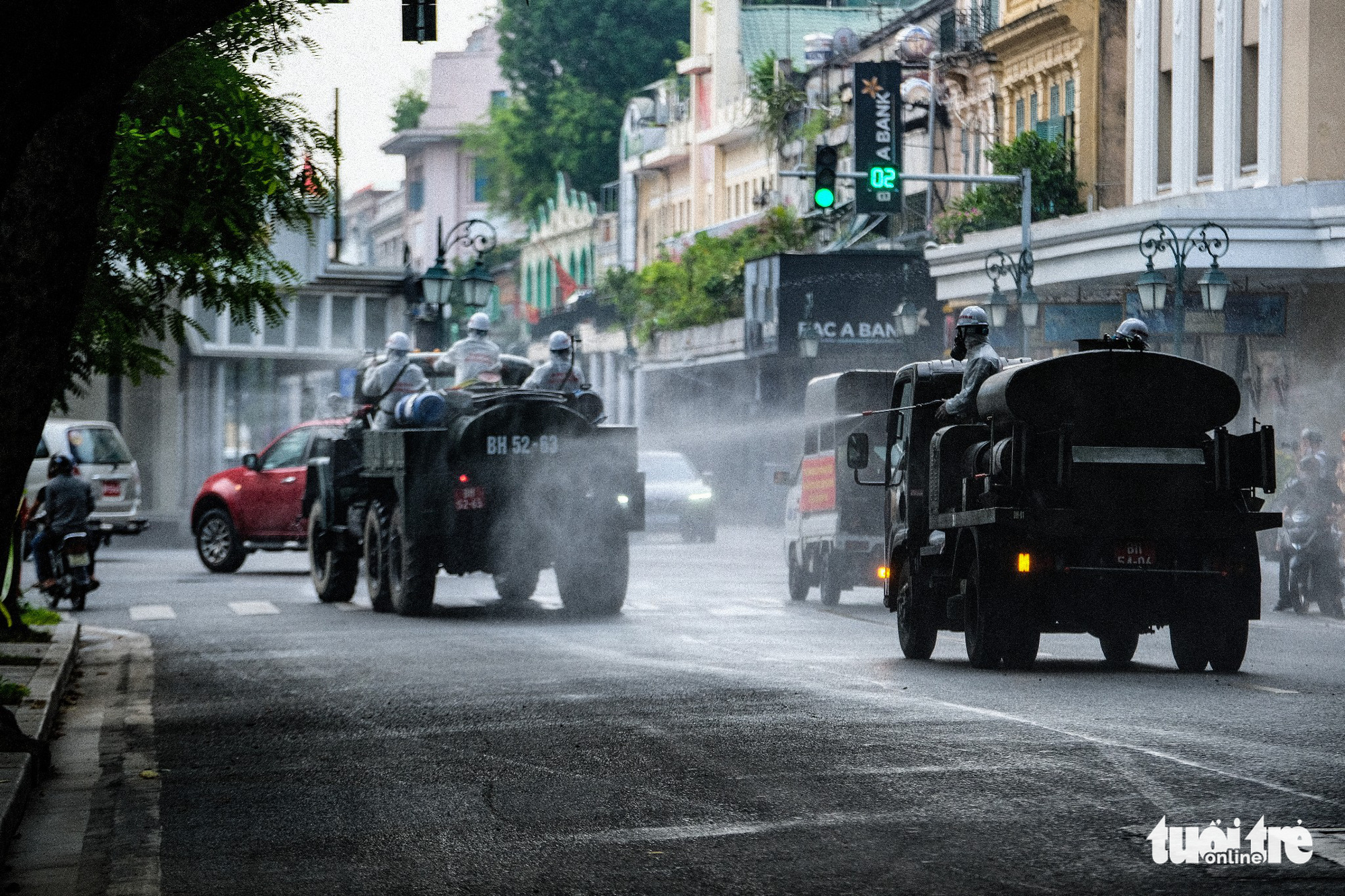 This image shows specialized vehicles spraying chemicals to disinfect a street in Hoan Kiem District, Hanoi, July 26, 2021. Photo: Nam Tran / Tuoi Tre