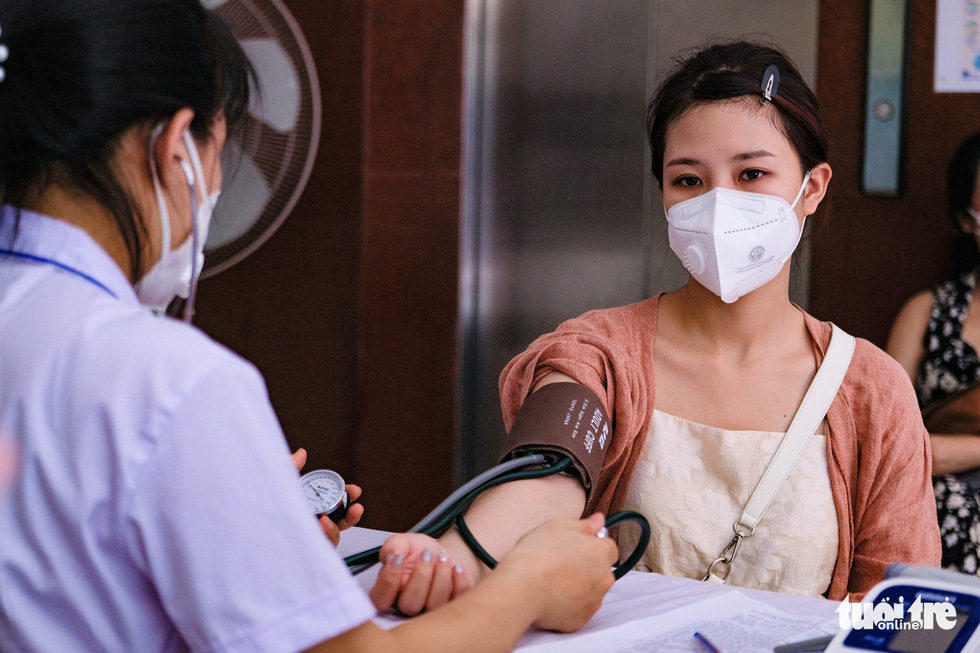 A health worker measures a woman's blood pressure ahead of a COVID-19 vaccination session in Hoan Kiem District, Hanoi, July 27, 2021. Photo: Nam Tran / Tuoi Tre