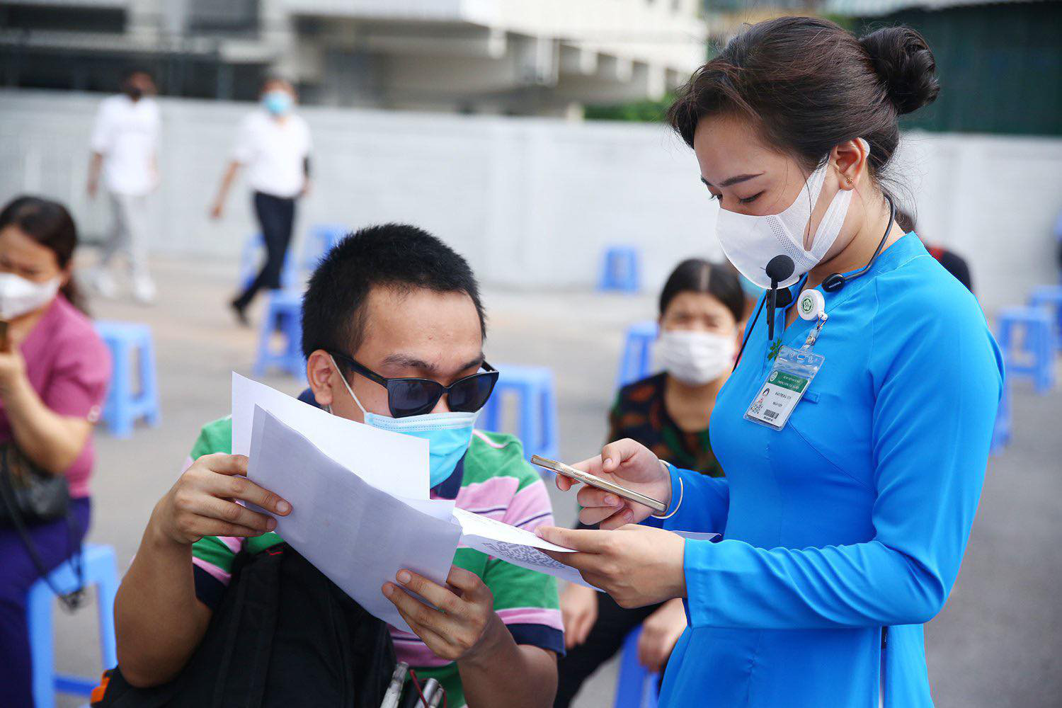 A staff member assists a disabled worker with paperwork before a COVID-19 vaccination session in Hanoi, July 29, 2021. Photo: Ministry of Planning and Investment
