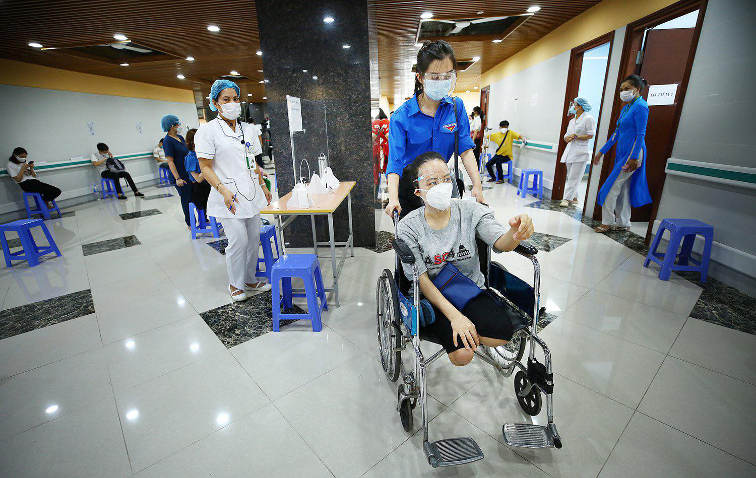 A volunteer moves a disabled worker on a wheel chair to a COVID-19 vaccination room in Hanoi, July 29, 2021. Photo: Ministry of Planning and Investment