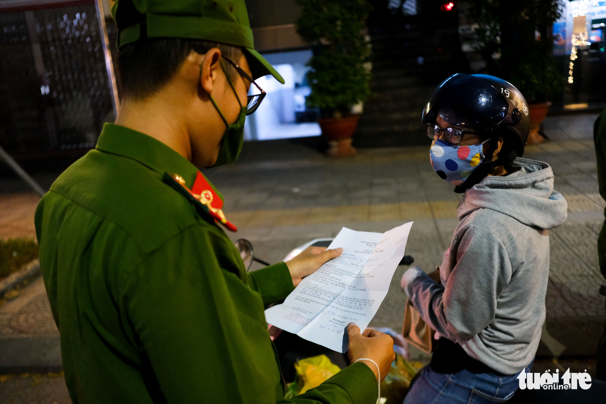 An officer checks documents of a commuter in Da Nang, July 31, 2021. Photo: Tan Luc / Tuoi Tre