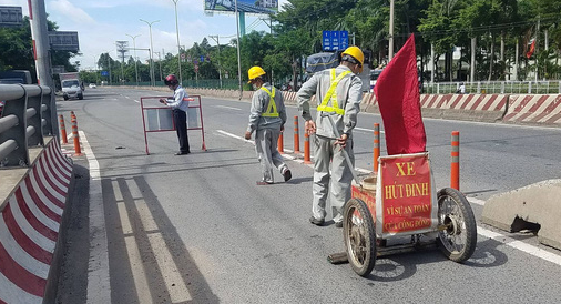 Employees of Infrastructure Development Investment JSC remove tire-puncturing nails from a road in Binh Tan District, Ho Chi Minh City, August 1, 2021. Photo: A.X. / Tuoi Tre