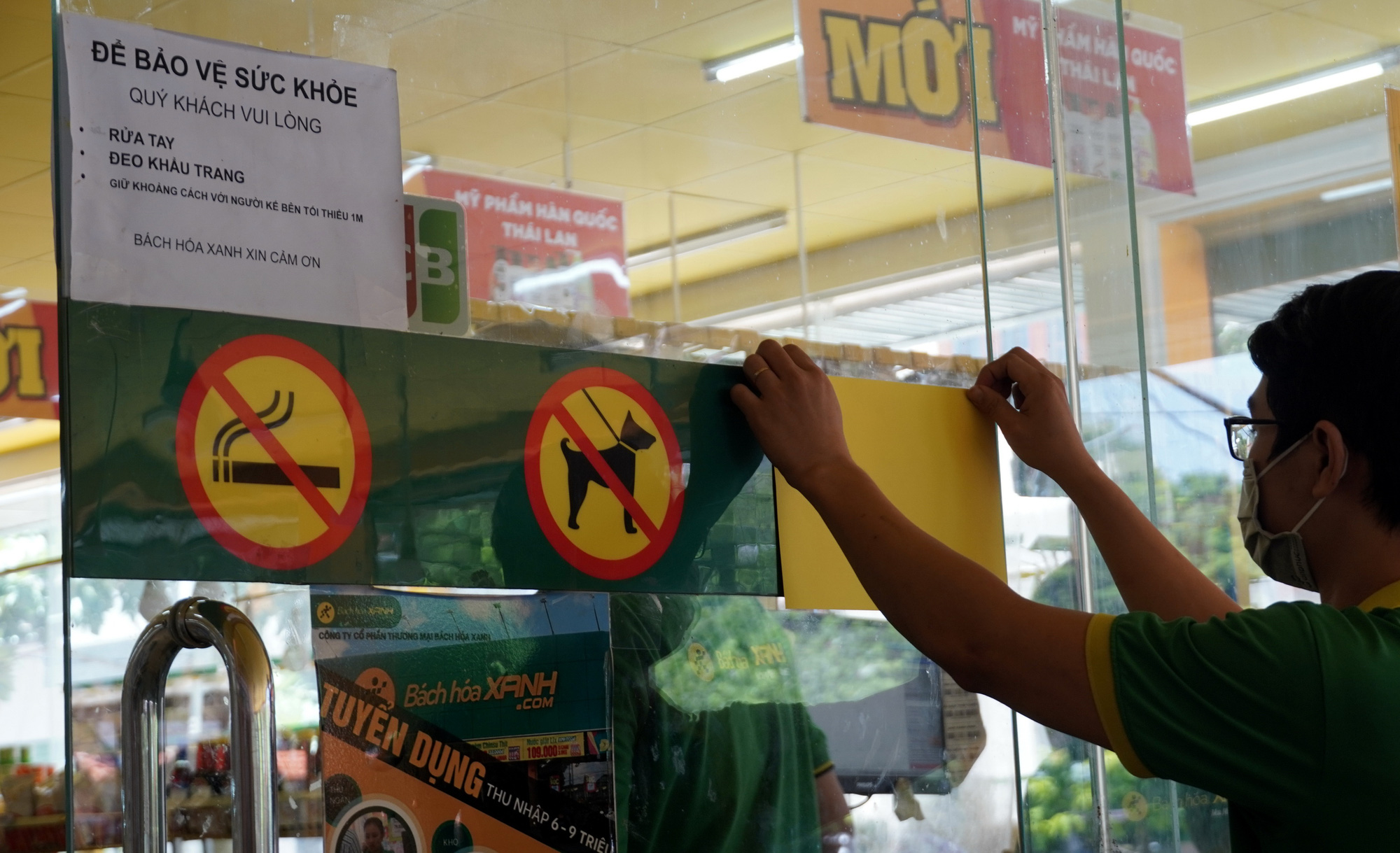 A worker covers a 'no photography' sign on the door of a Bach Hoa Xanh store in Ba Ria - Vung Tau Province, Vietnam. Photo: D.H. / Tuoi Tre