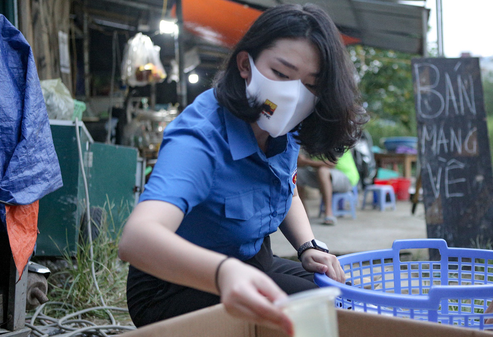 A young volunteer helps to deliver rice meals to the needy. Photo: Ha Quan / Tuoi Tre