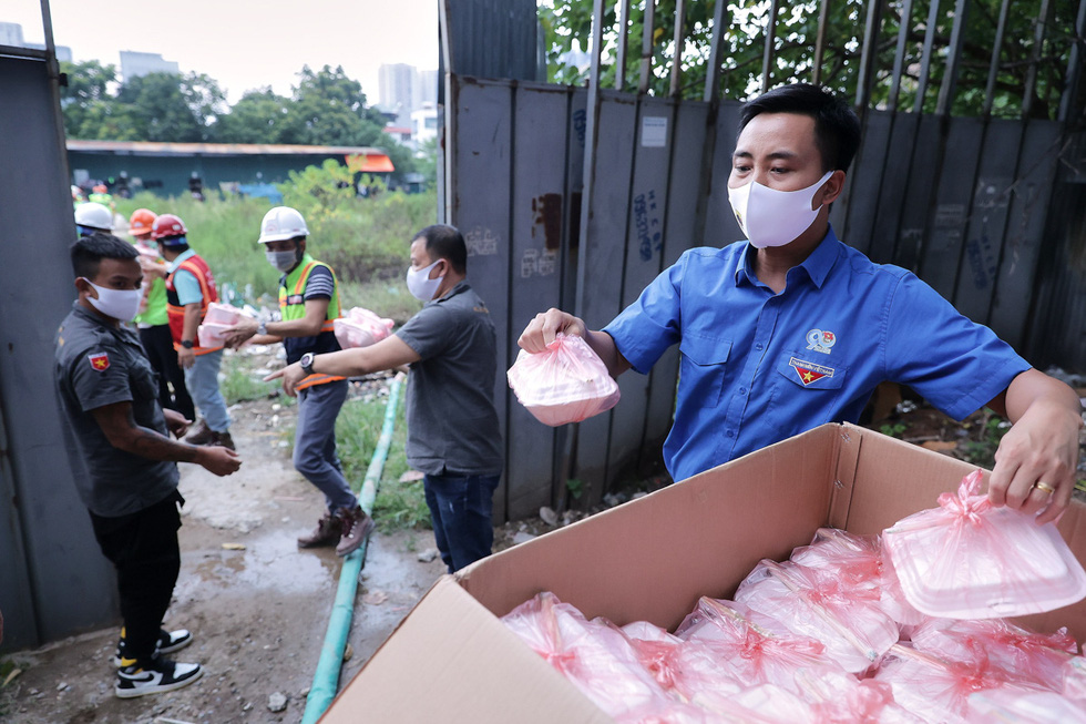 Cartons filled with free meals have been transported to the entrance of a construction site where the workers live and work in the Ha Dong District. Photo: Ha Quan / Tuoi Tre