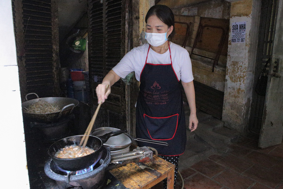 Yen, a member of the group, stirs food in a frying pan. She and her husband had to stop selling rice due to the pandemic, so Yen feels happy to use her cooking skills to help others. Photo: Ha Quan / Tuoi Tre