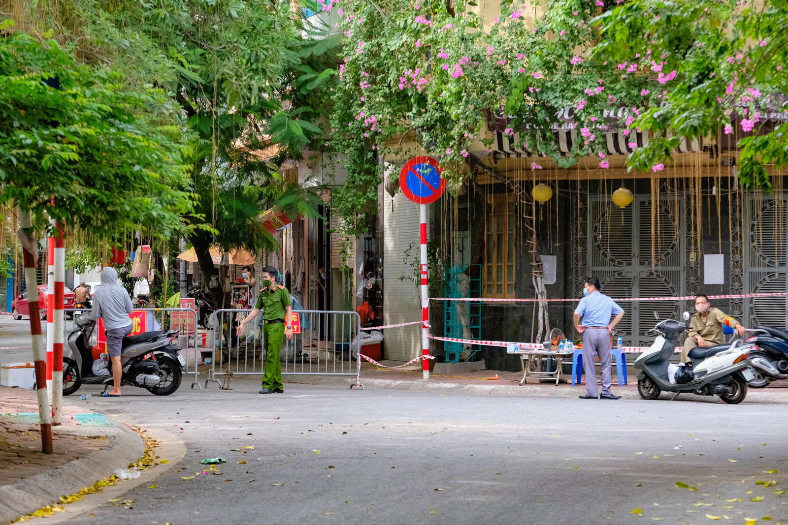 Officers guard an entrance to a locked-down residential area in Dong Da District, Hanoi, August 5, 2021. Photo: Nam Tran / Tuoi Tre