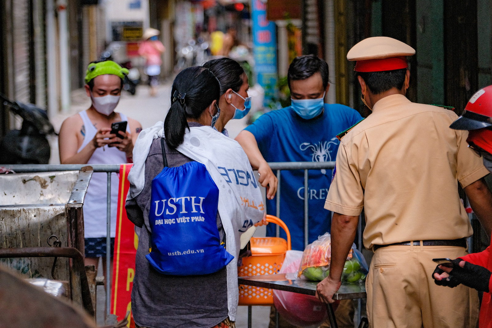 People receive food through a barricade set up at an entrance to a locked-down residential area in Dong Da District, Hanoi, August 5, 2021. Photo: Nam Tran / Tuoi Tre