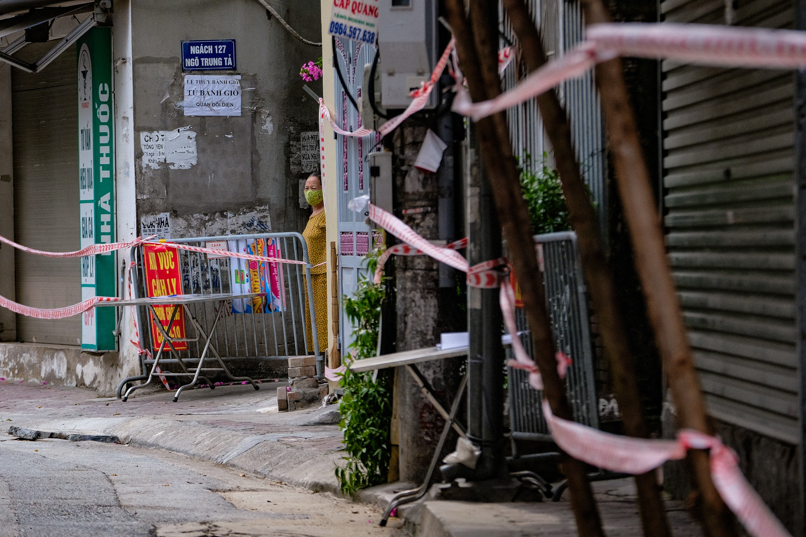 A woman looks out from a locked-down corner in Dong Da District, Hanoi, August 5, 2021. Photo: Nam Tran / Tuoi Tre