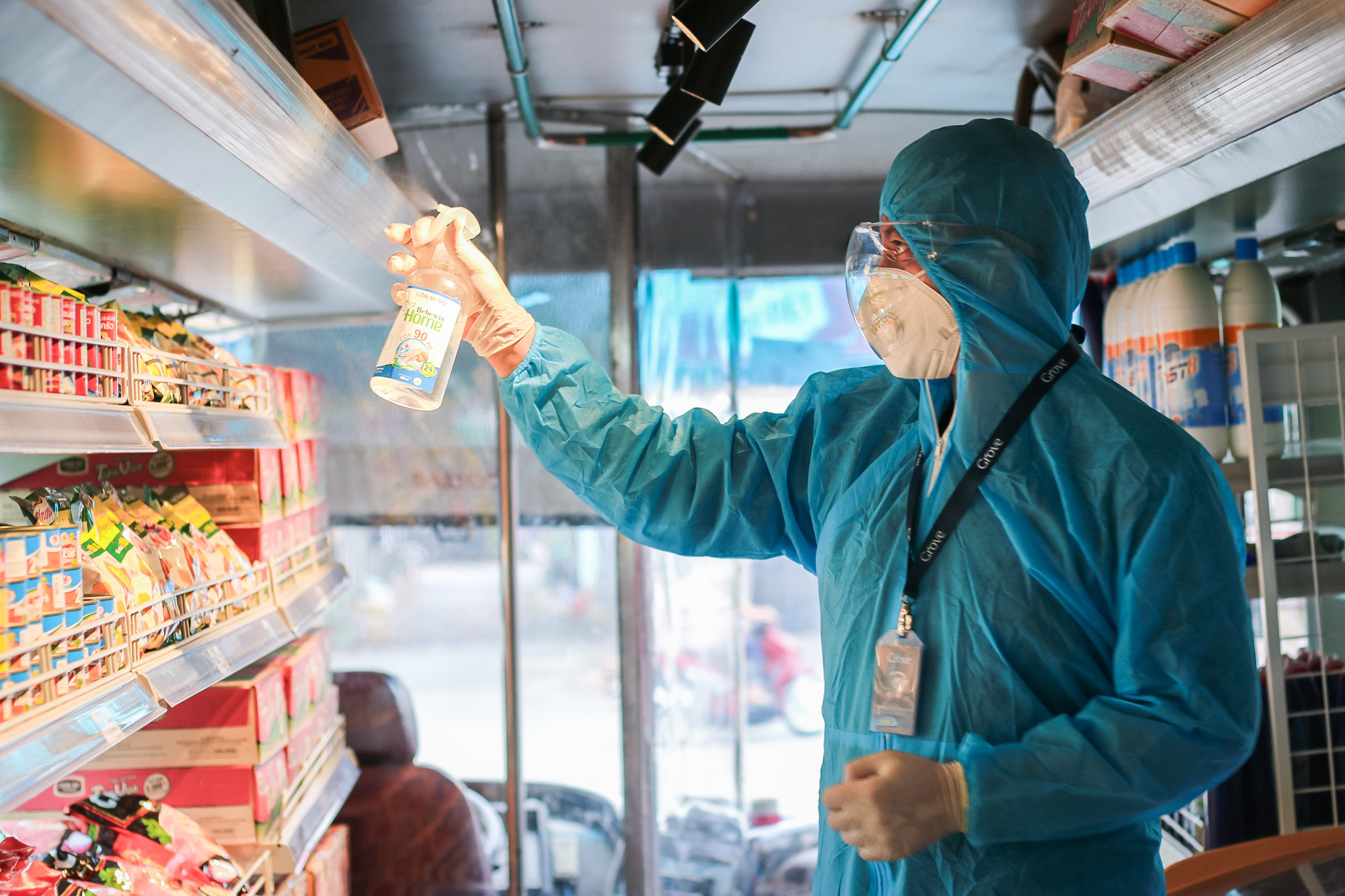 An employee disinfects the shelves after customers exit the mobile mini-supermarket. Photo: Kim Ut / Tuoi Tre