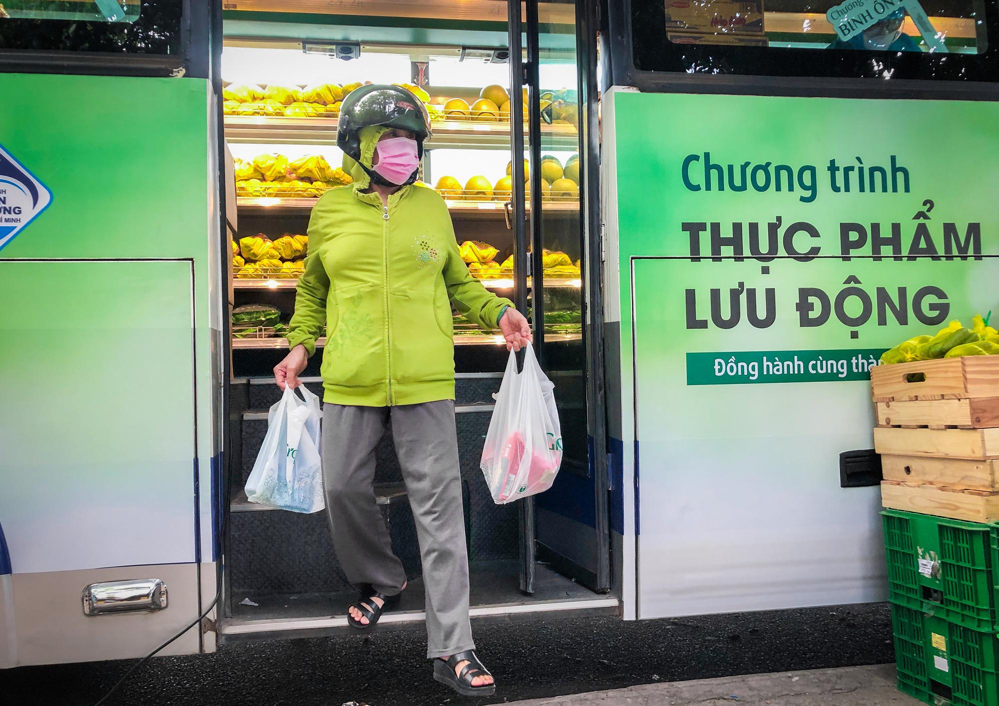 A customer exits the mobile mini-supermarket. Photo: Kim Ut / Tuoi Tre